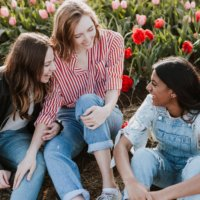 Photo of three young women talking and laughing outside