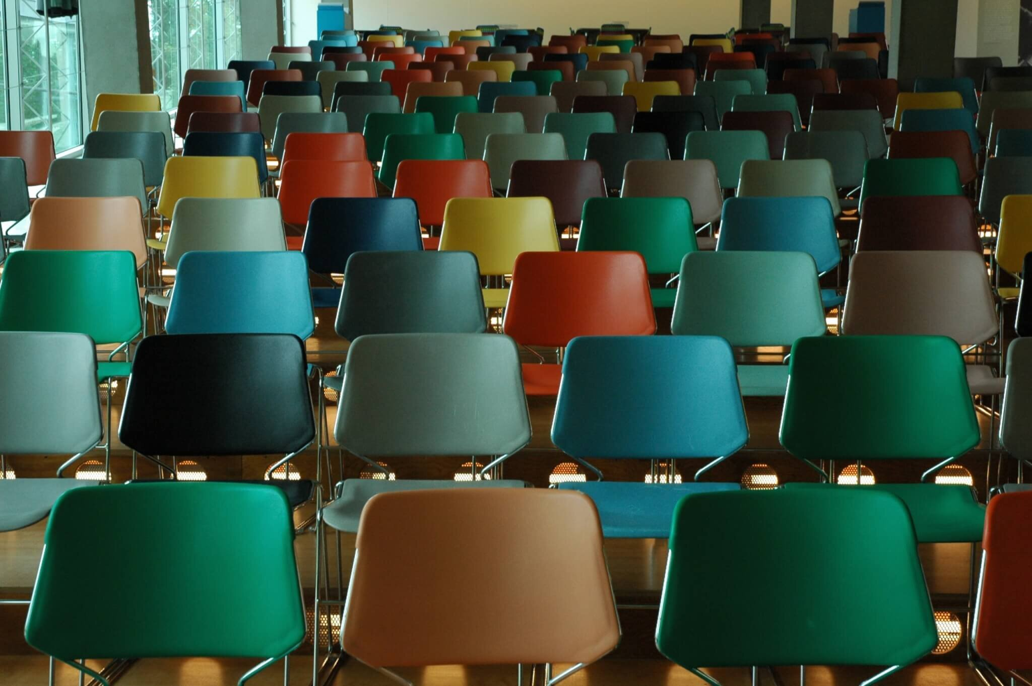 Image of an empty lecture hall with colourful chairs